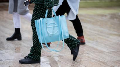 A guest is seen carrying a blue Telfar Shopping Bag outside a show at Paris Fashion Week