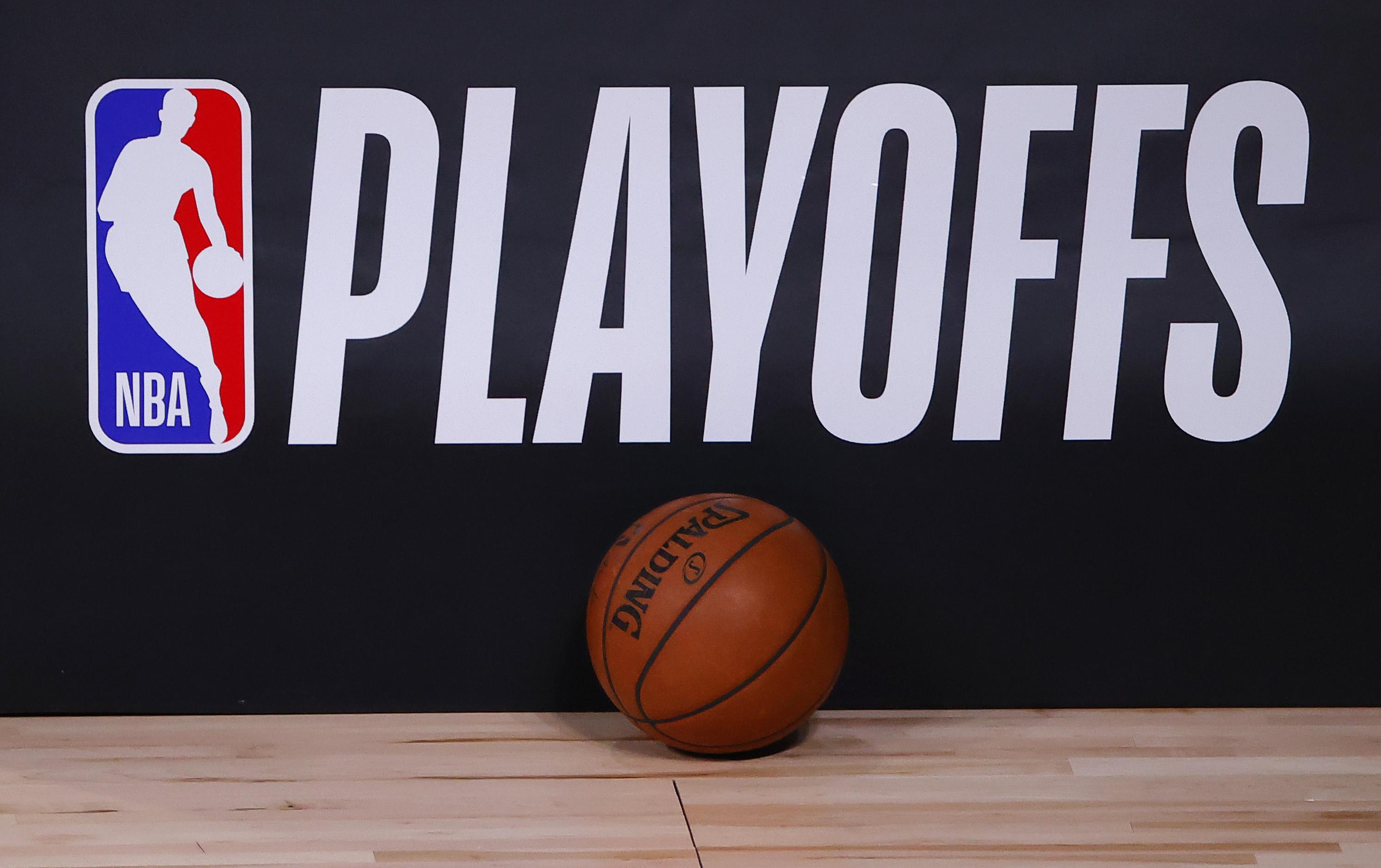 A basketball sits next to an NBA Playoffs logo