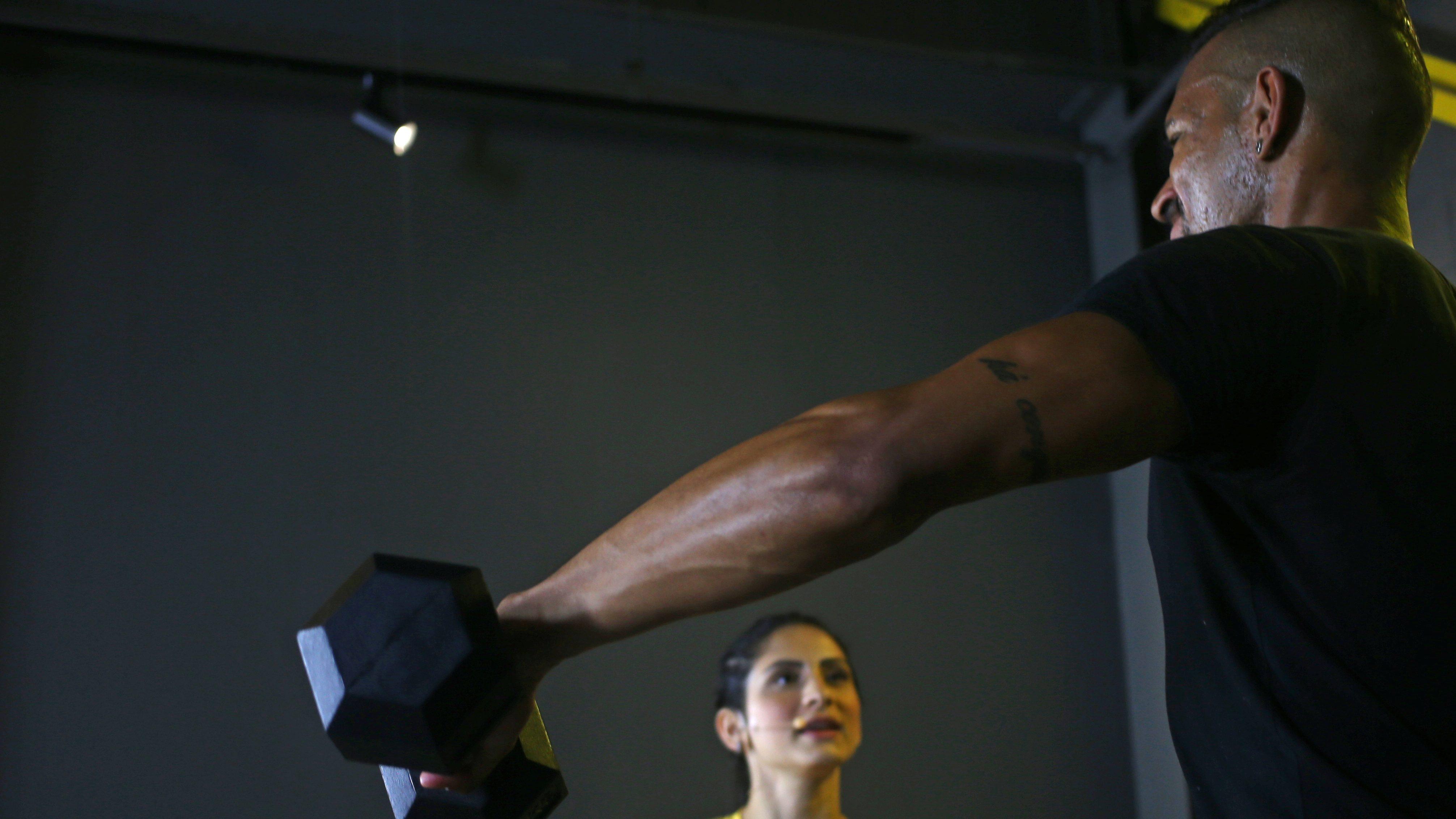 A man lifts a dumbbell.