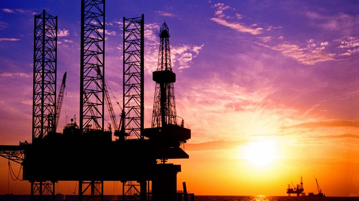 An image of a deepwater oil rig with a sunset in the background.