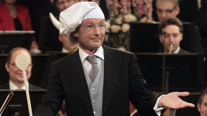 Maestro Franz Welser-Moest conducts the Vienna Philharmonic Orchestra with a wooden spoon as he wears a chef's hat, during the traditional New Year's Concert in the Golden Hall of the Vienna Musikverein in Vienna