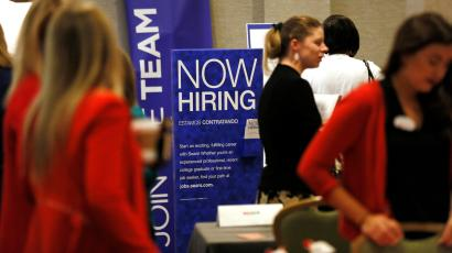 """Several women mill around a job fair near a bright blue sign that says """"Now Hiring"""". The two women in the foreground wear red dresses and cardigans; the blond woman in the back with a ponytail is wearing black."""