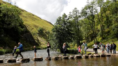 Walkers cross the Dovedale stepping stones in the Peak District in August 2017.
