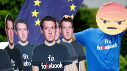 """A protester wearing a shirt that reads """"fix fakebook"""" and a mask that looks like Facebook's """"angry reaction"""" stands next to cardboard cutouts depicting Facebook CEO Mark Zuckerberg"""