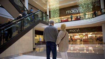 A couple holds hands in front of a Macy's store in a mall