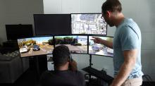 A man sits in front of five computer monitors showing different displays from a self driving car while a colleague peers over his shoulder.