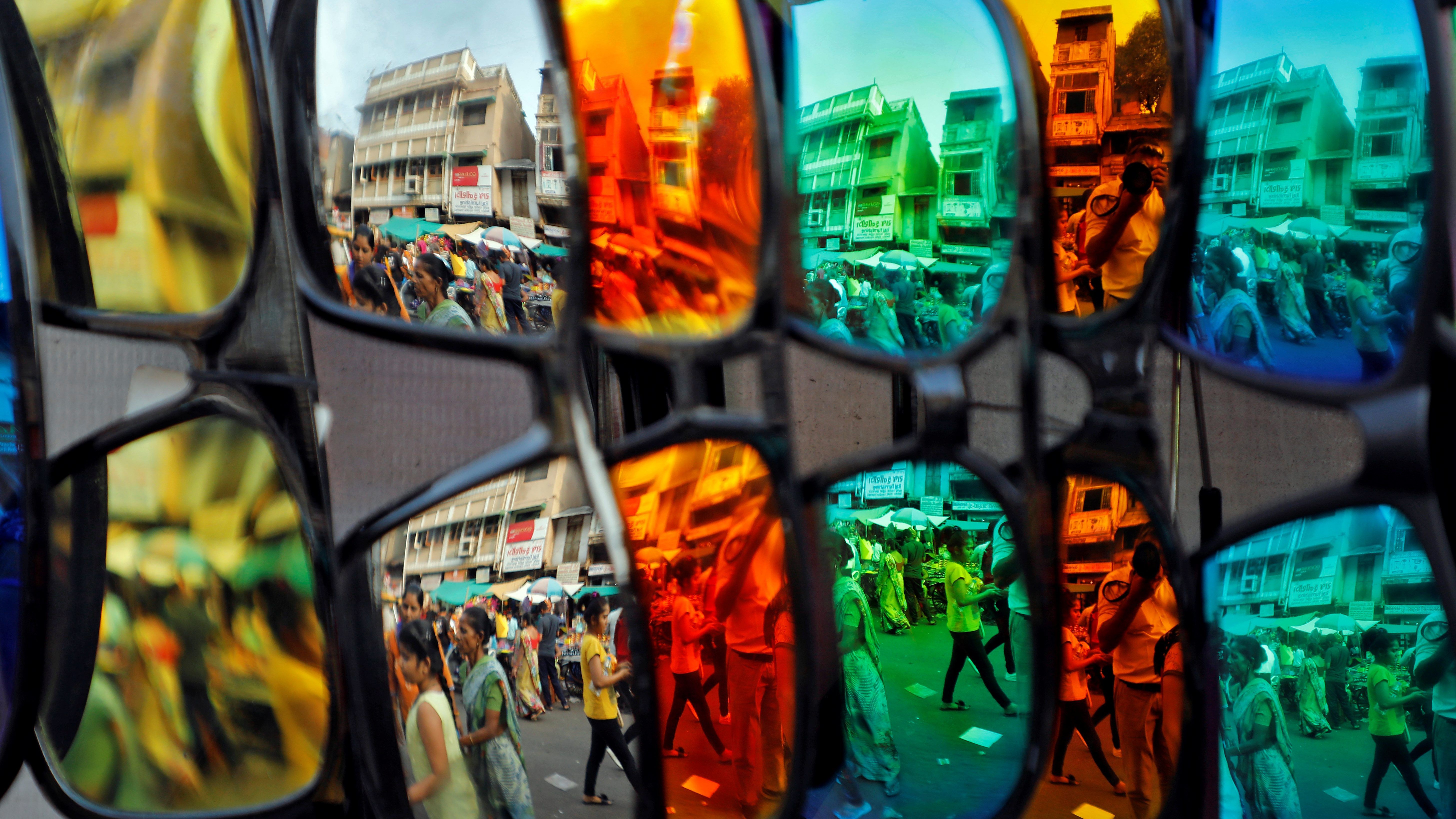 Shoppers are reflected in sunglasses on display for sale at a market place ahead of Diwali in Ahmedabad