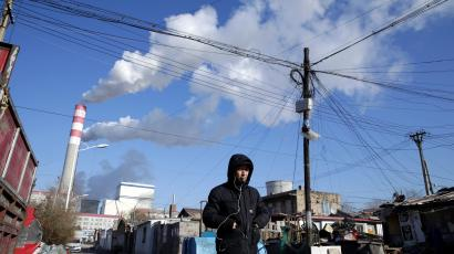A man walks past a coal-fired power plant in China. The country is building hundreds of new coal plants in spite of its new climate goals.