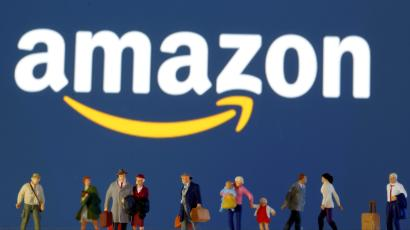 FILE PHOTO: Small toy figures are seen in front of diplayed Amazon logo