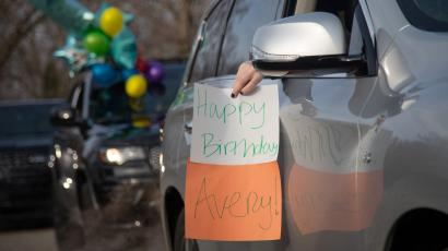 "The left side of a grey SUV with the windows down. A person with black painted finger nails holds out a sign that says ""Happy Birthday Avery"" out of the window. The car behind it has balloons hanging out the window."