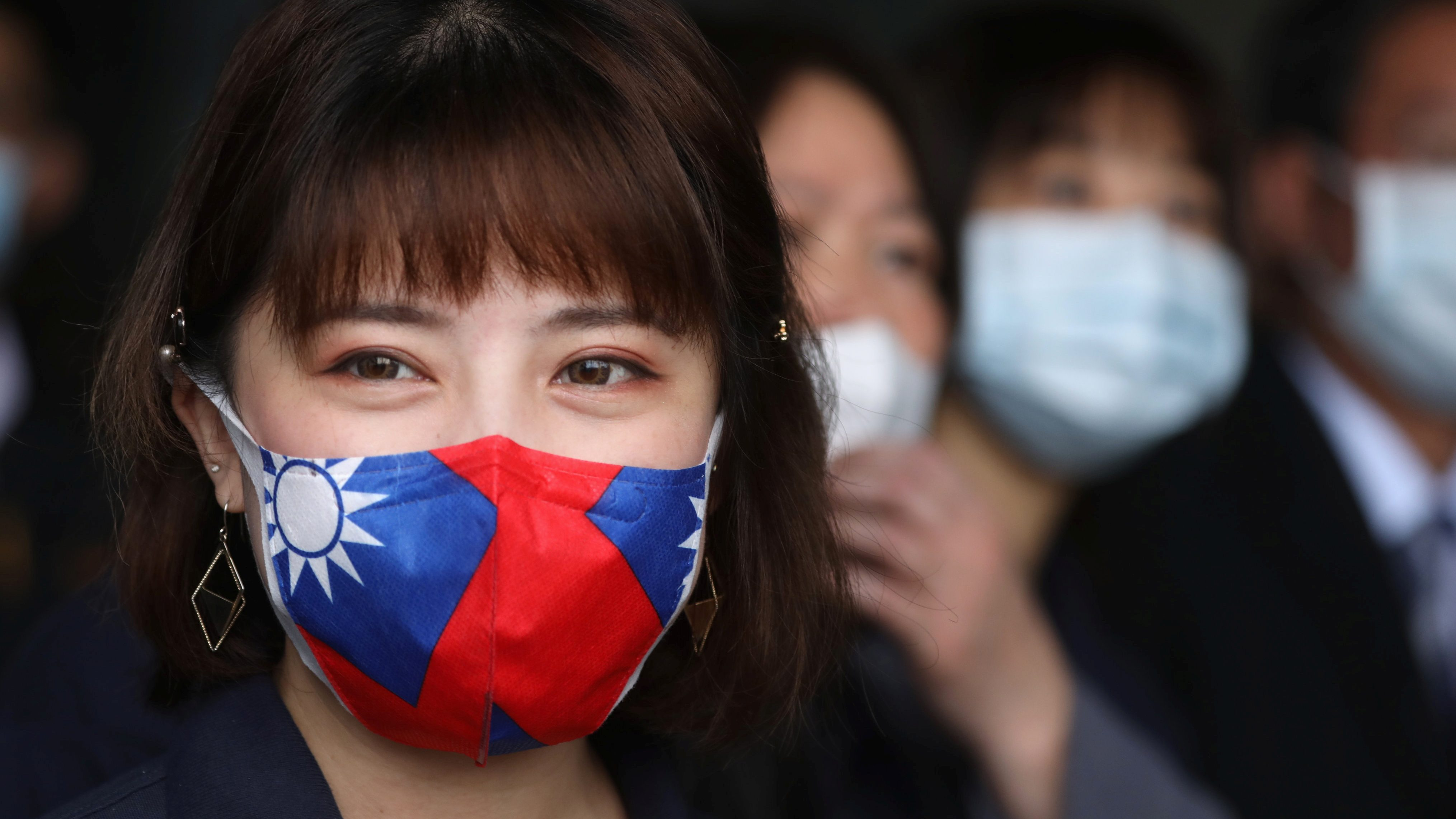 A factory employee wears a face mask with a Taiwanese flag design, as protection due to the coronavirus disease (COVID-19) outbreak, at a factory for non woven filter fabric used to make surgical face masks, in Taoyuan, Taiwan, March 30, 2020.