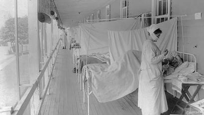 A nurse takes the pulse of a patientin the influenza ward at Walter Reed Hospital during the Spanish Flu pandemic