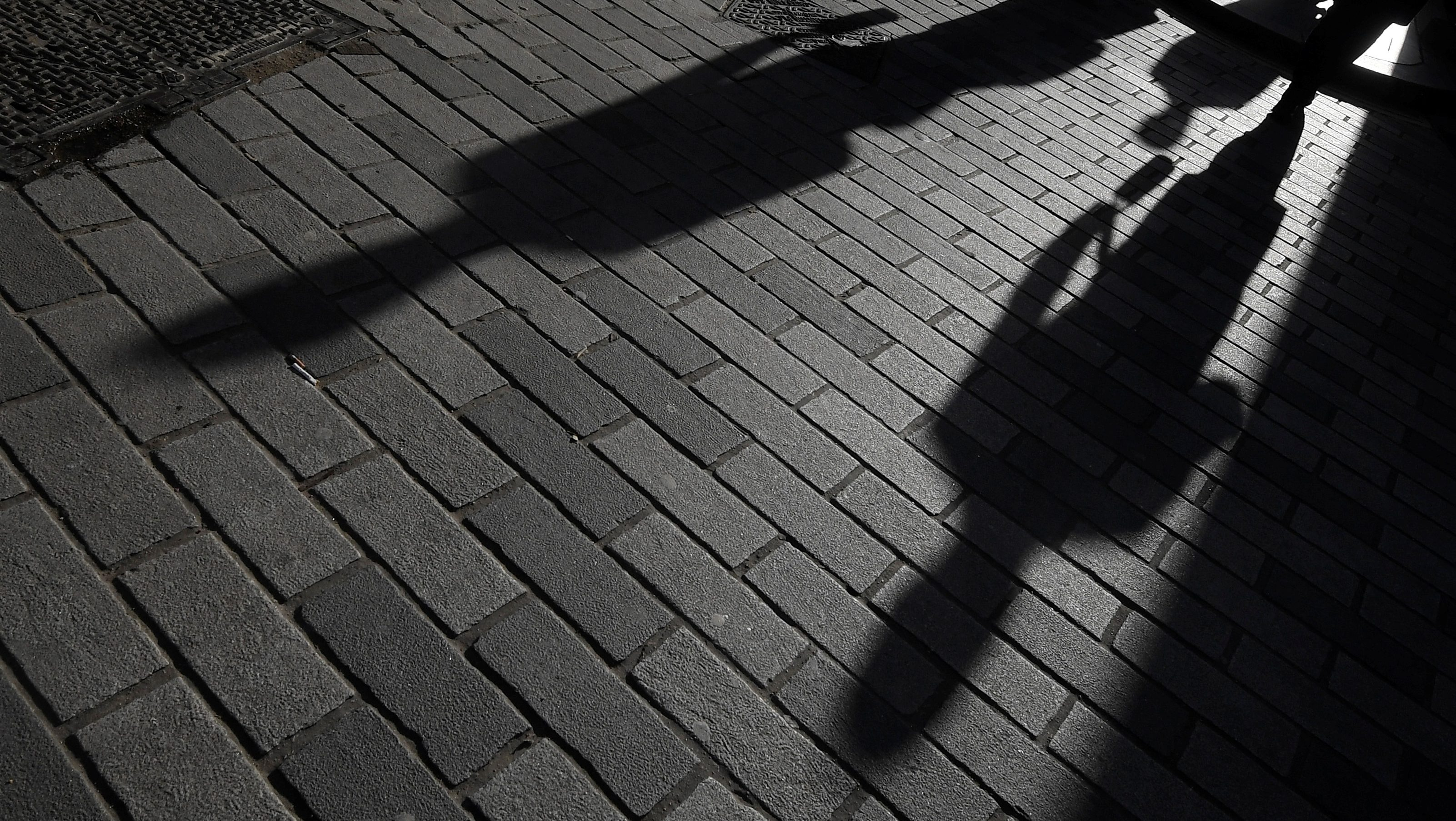 Image of shadows on a cobblestone street. Cities are housing victims of domestic violence in hotels.