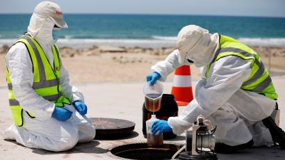 Two people in full PPE and yellow safety vests pour out wastewater into a collection jar from a manhole. There's a beach behind the road, and there's clear blue water and waves in the background. It's a sunny day.