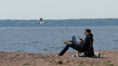 A man uses his smartphone and laptop as he sits on the shore of the Gulf of Finland amid the outbreak of the coronavirus disease (COVID-19) in Saint Petersburg, Russia May 27, 2020.