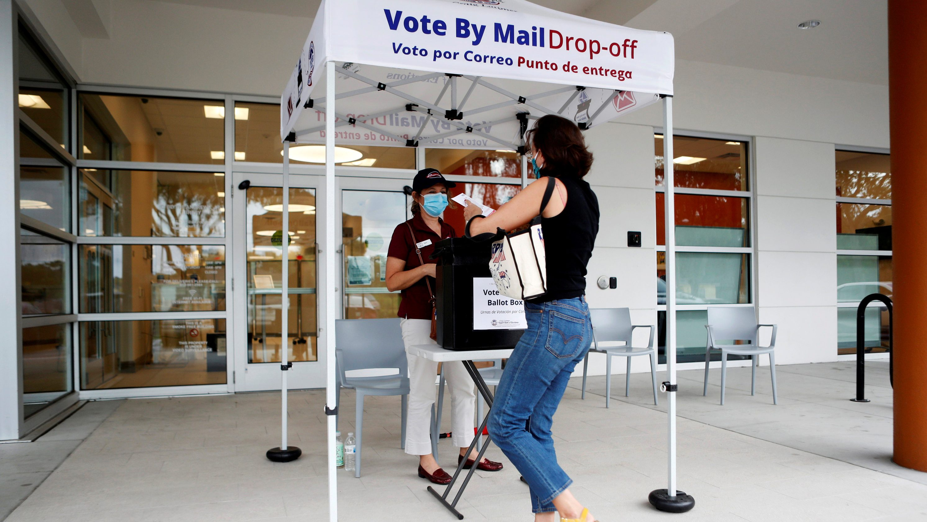 A woman prepares to cast her mail-in voter ballot the last day of early voting for the U.S. presidential election in Florida
