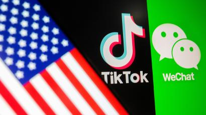 A U.S. flag is seen on a smartphone in front of displayed Tik Tok and WeChat logos.