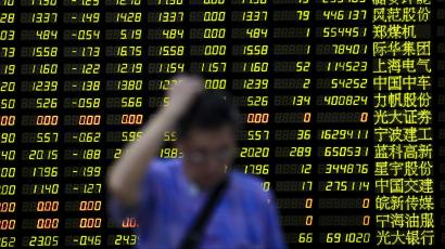 An investor stands in front of an electronic board showing stock information at a brokerage house in Shanghai, China.