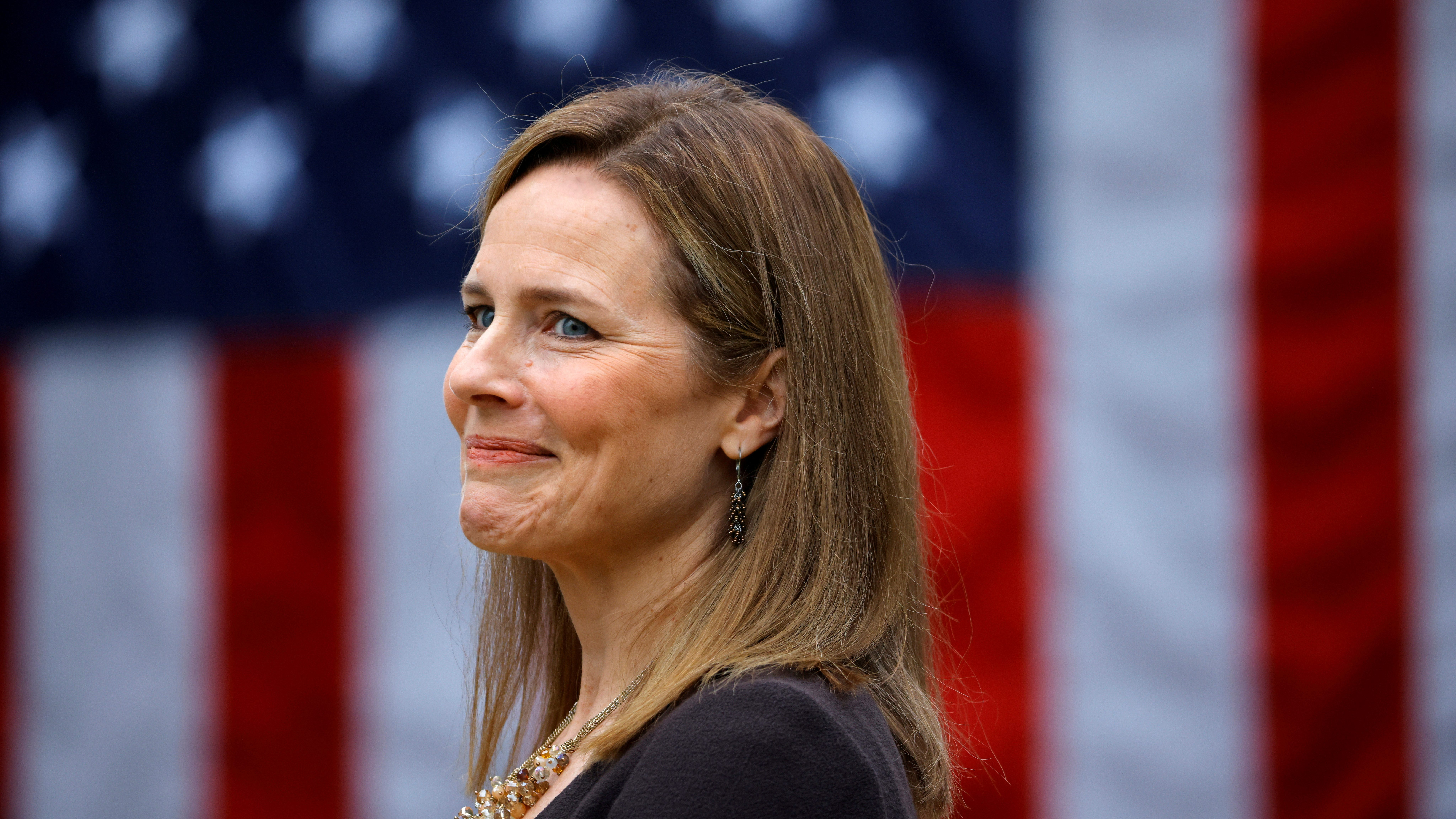 A close-up picture of Supreme Court nominee Amy Coney Barrett, a US Court of Appeals Seventh Circuit Judge, in front of an American flag during the presidential announcement event.