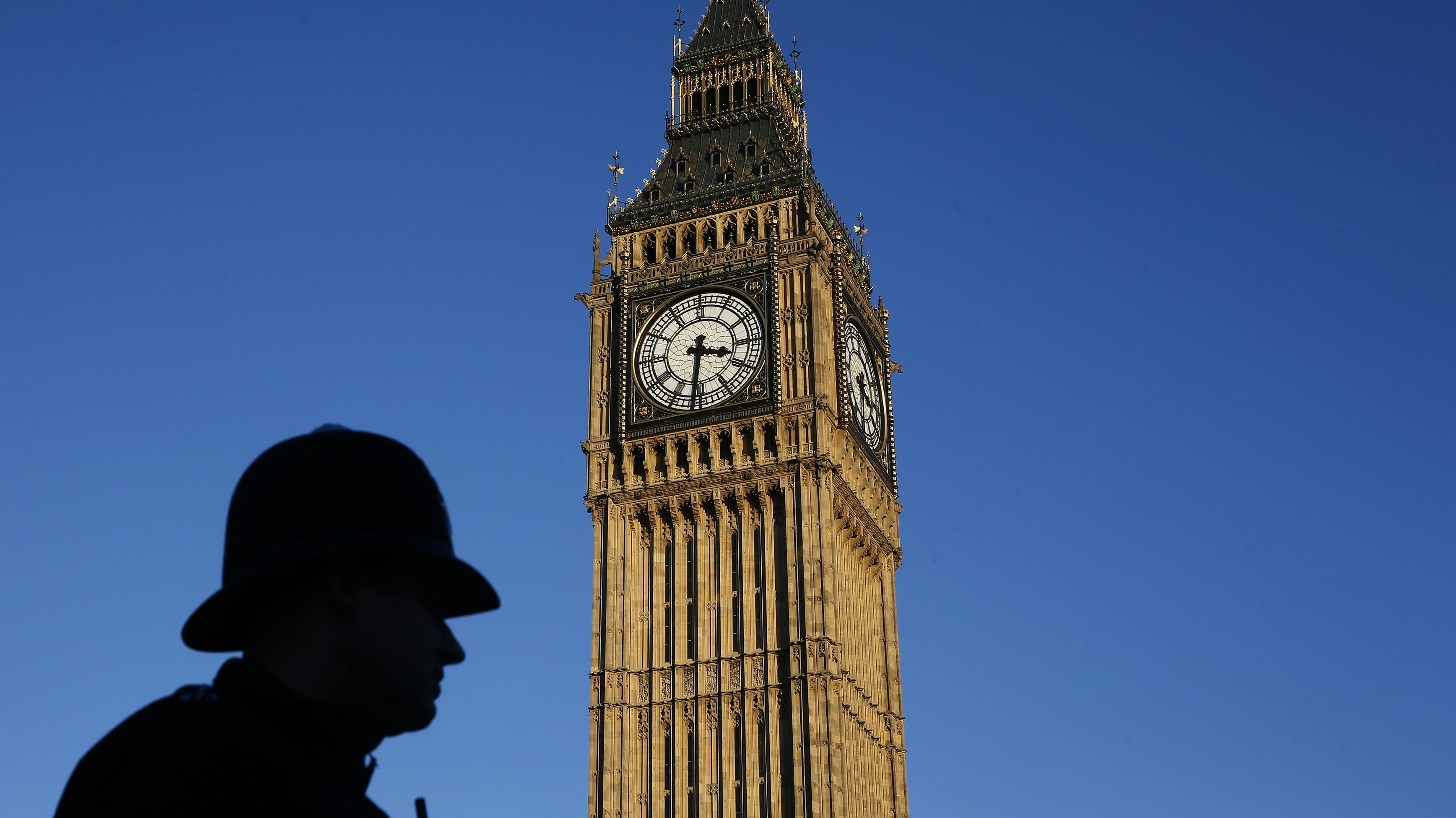 A police officer is silhouetted against the sky next to the Big Ben clock tower during sunset in central London.