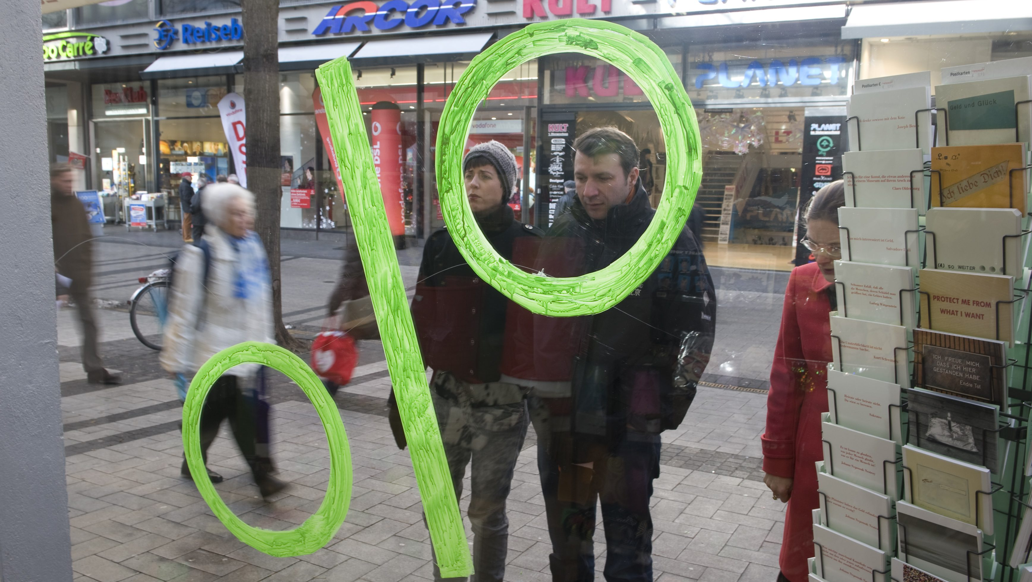 People are seen through a percentage sign as they stand in front of a shopping window in downtown Cologne
