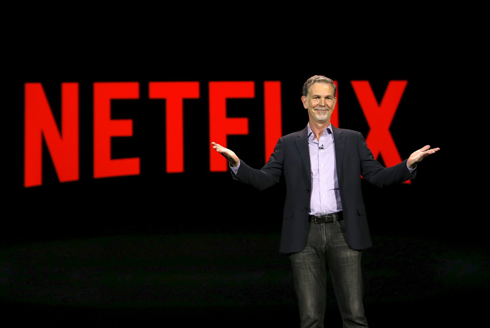 Netflix co-founder and co-CEO Reed Hastings in front of a Netflix logo