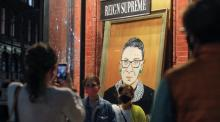 Children are photographed in front of a painting in a storefront on Broadway of Associate Justice of the Supreme Court of the United States Ruth Bader Ginsburg who passed away in Manhattan, New York City