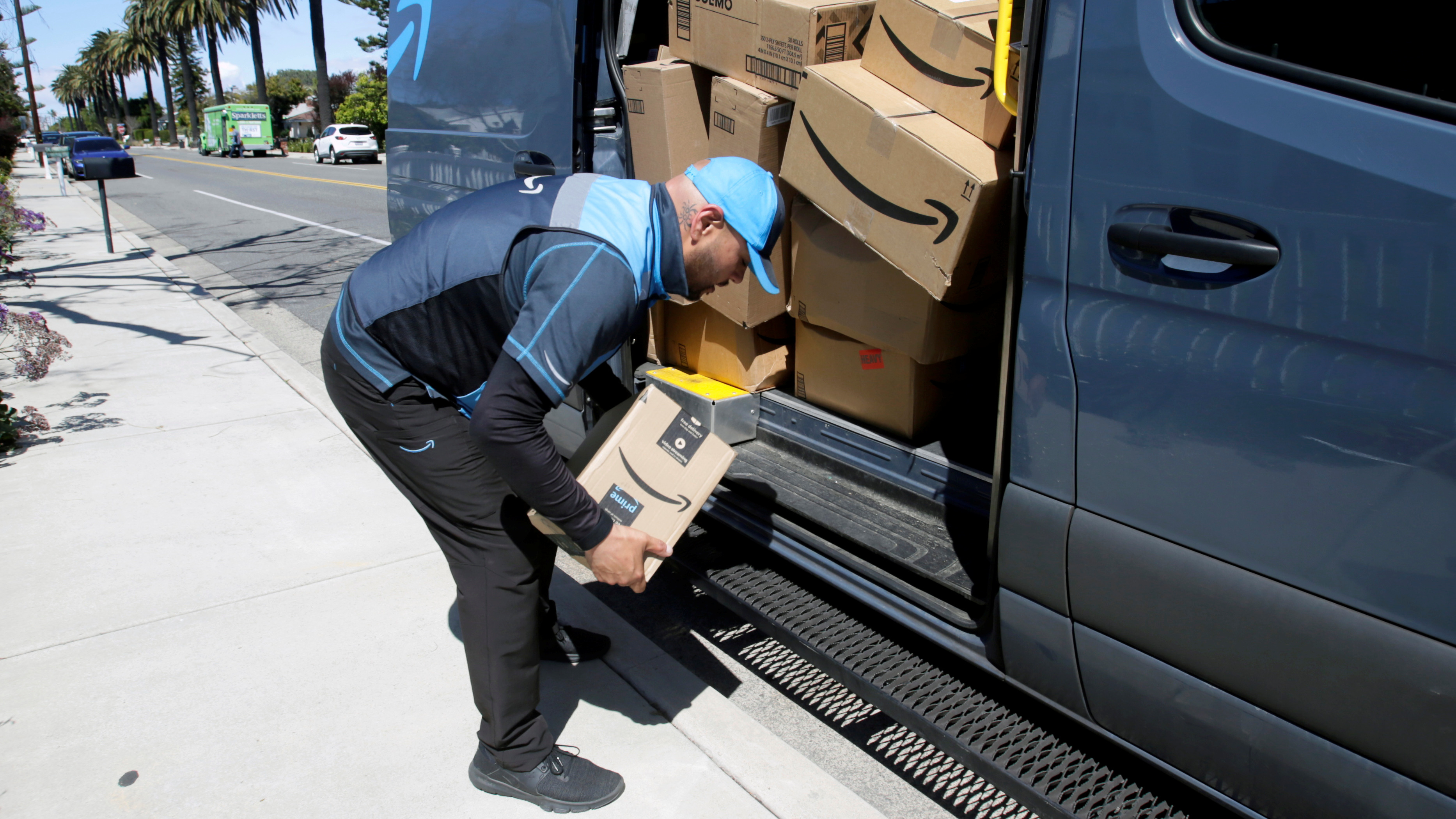 Joseph Alvarado picks up a package while making deliveries for Amazon during the outbreak of the coronavirus disease
