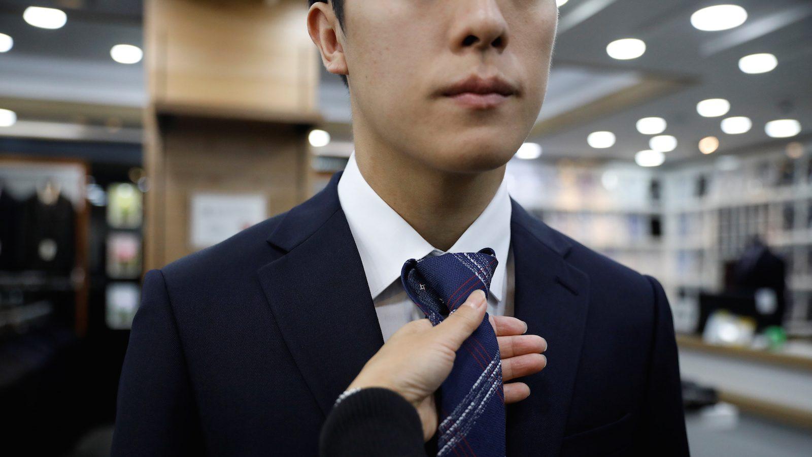man in suit tries on tie