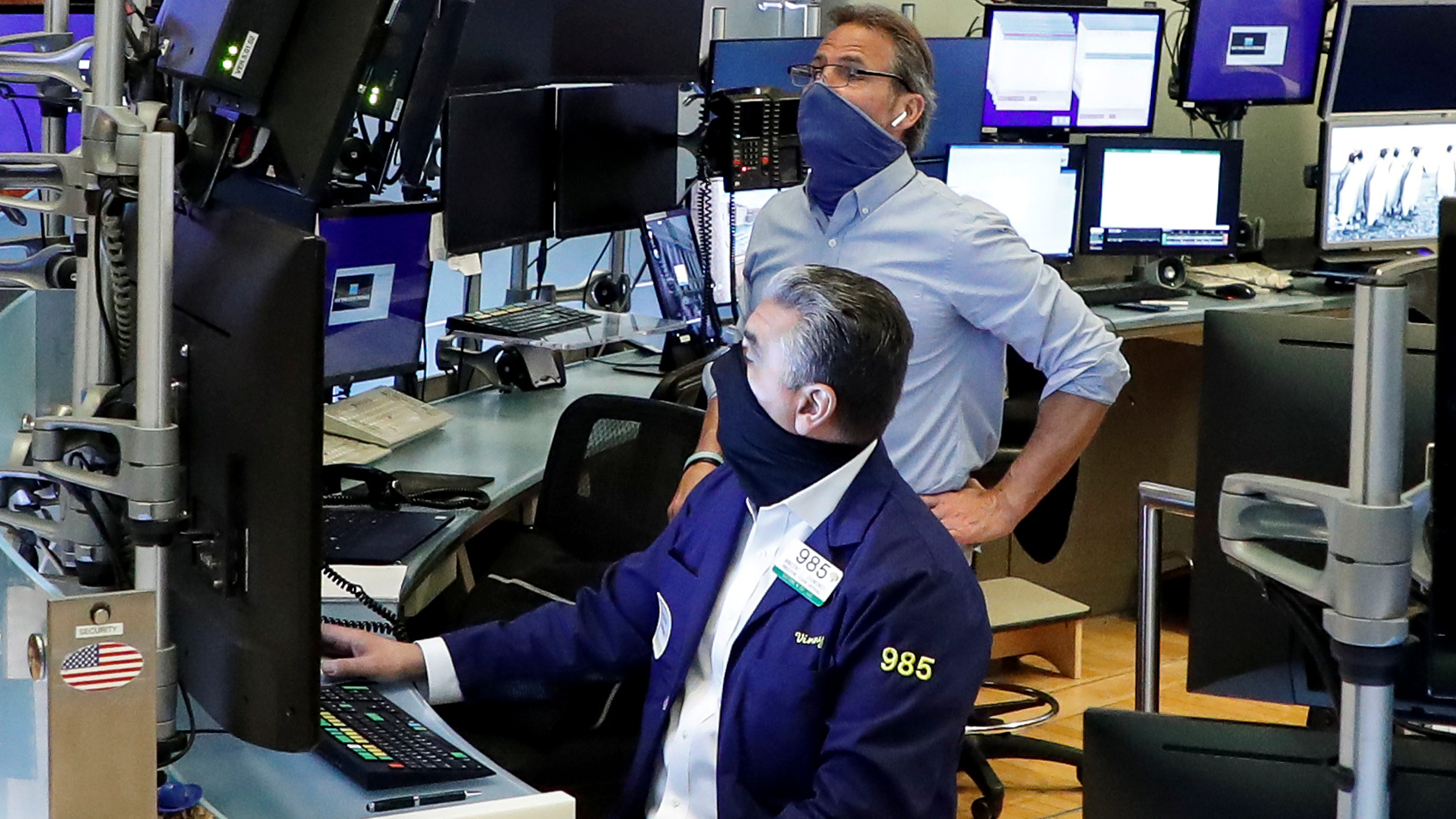 Traders wearing masks work, on the first day of in-person trading since the closure during the outbreak of the coronavirus disease (COVID-19) on the floor at the NYSE in New York