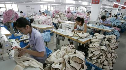 Laborers work on garments for export at the production line of a garment factory in Shanghai