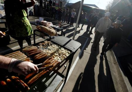 A line of voters stands behind a grill covered with sausages and onions