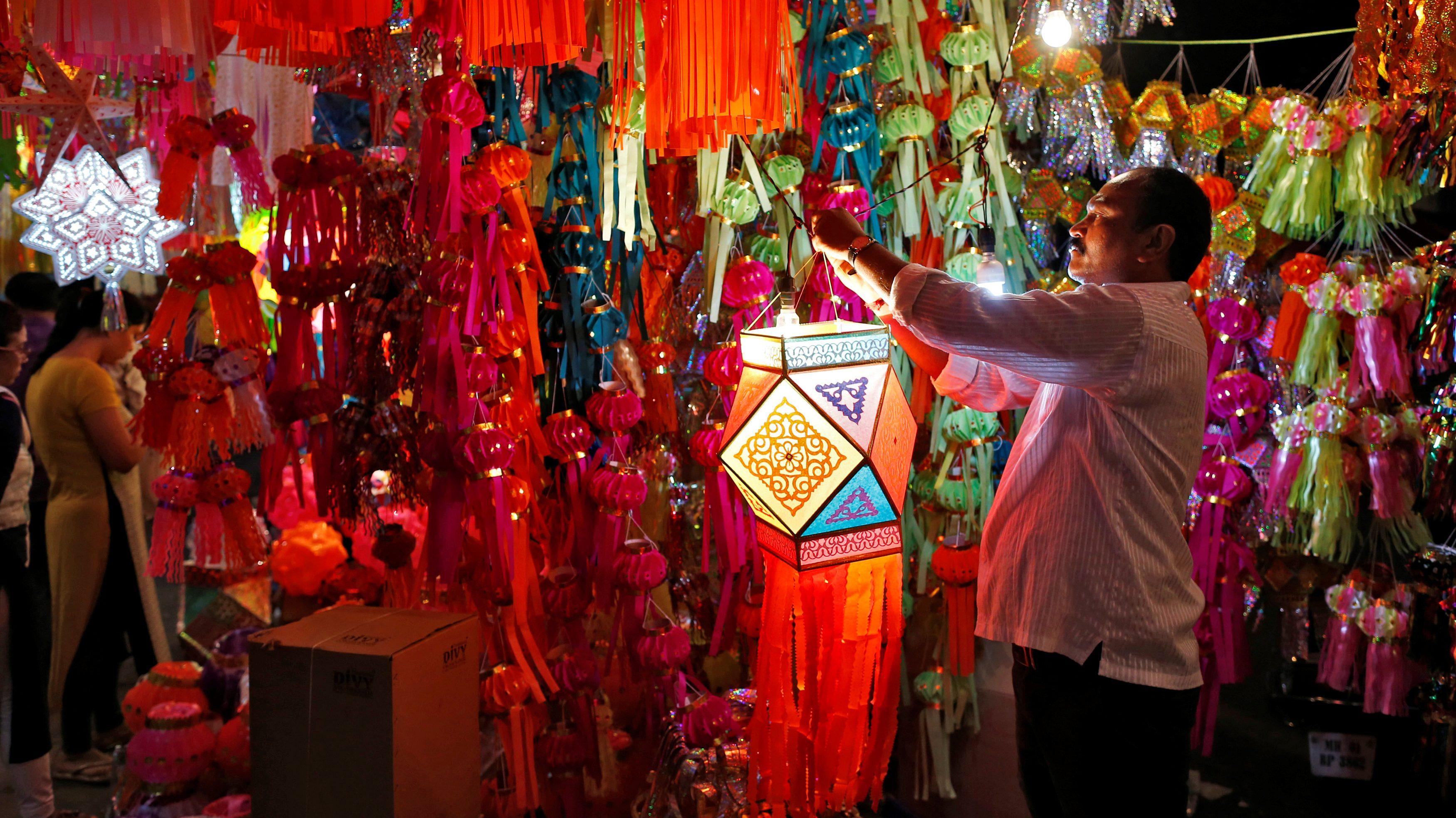 A vendor hangs a lantern for sale at a roadside market ahead of the Hindu festival of Diwali in Mumbai