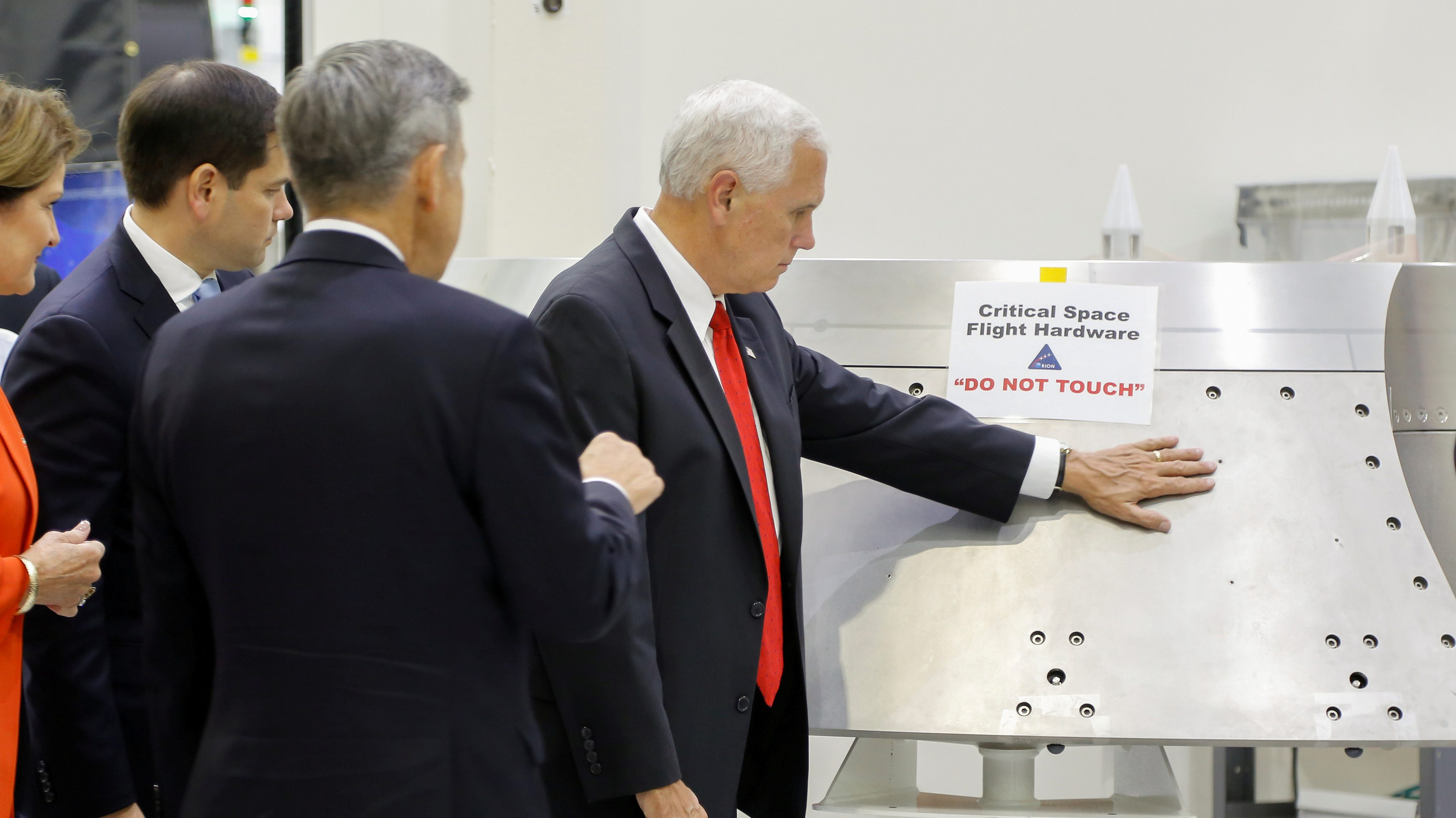"U.S. Vice President Mike Pence touches a piece of hardware with a warning label ""Do Not Touch"" at Kennedy Space Center."