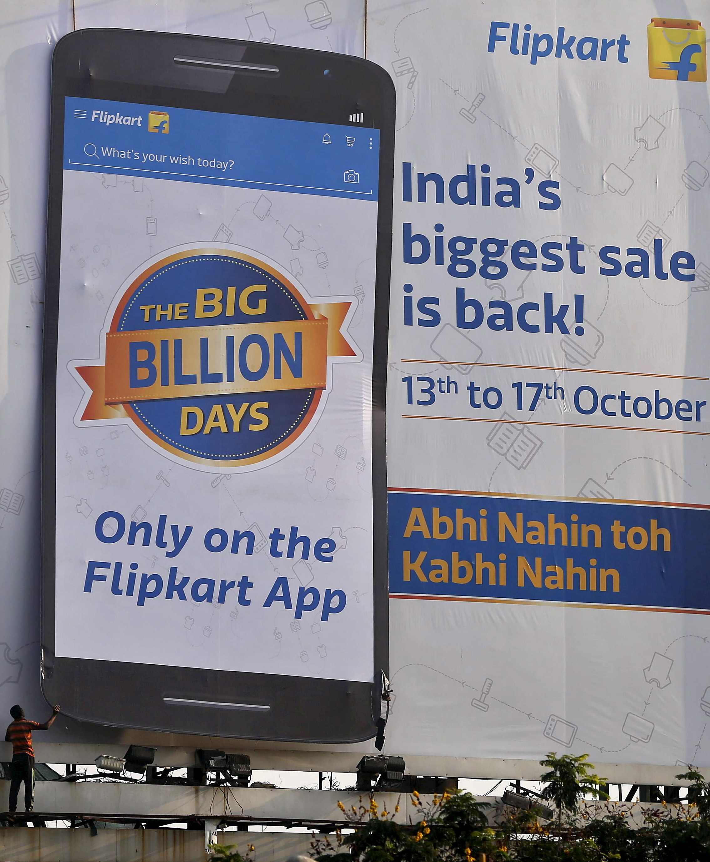 FILE PHOTO: A worker removes an advertisement billboard of Indian online marketplace Flipkart, installed along the roadside in Mumbai