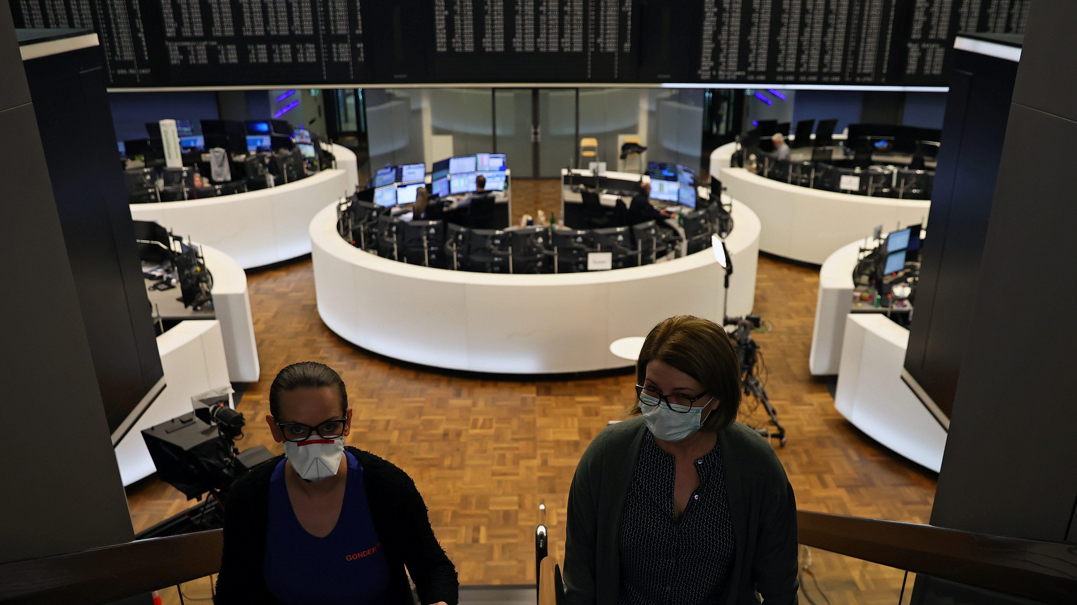 Women wear face masks at Frankfurt's stock exchange as markets.