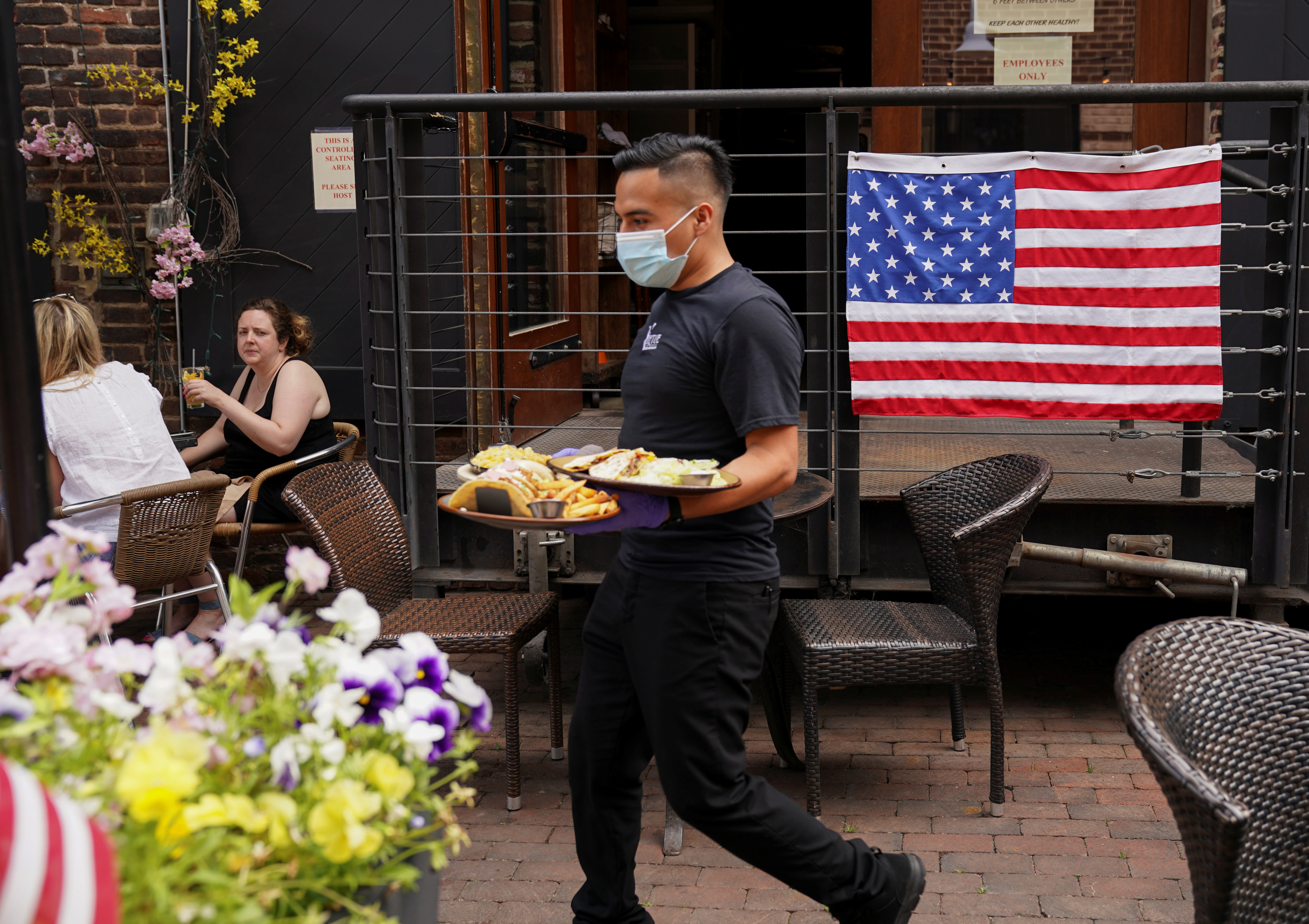 A waiter wearing a mask brings food to customers seated outside in front of an American flag