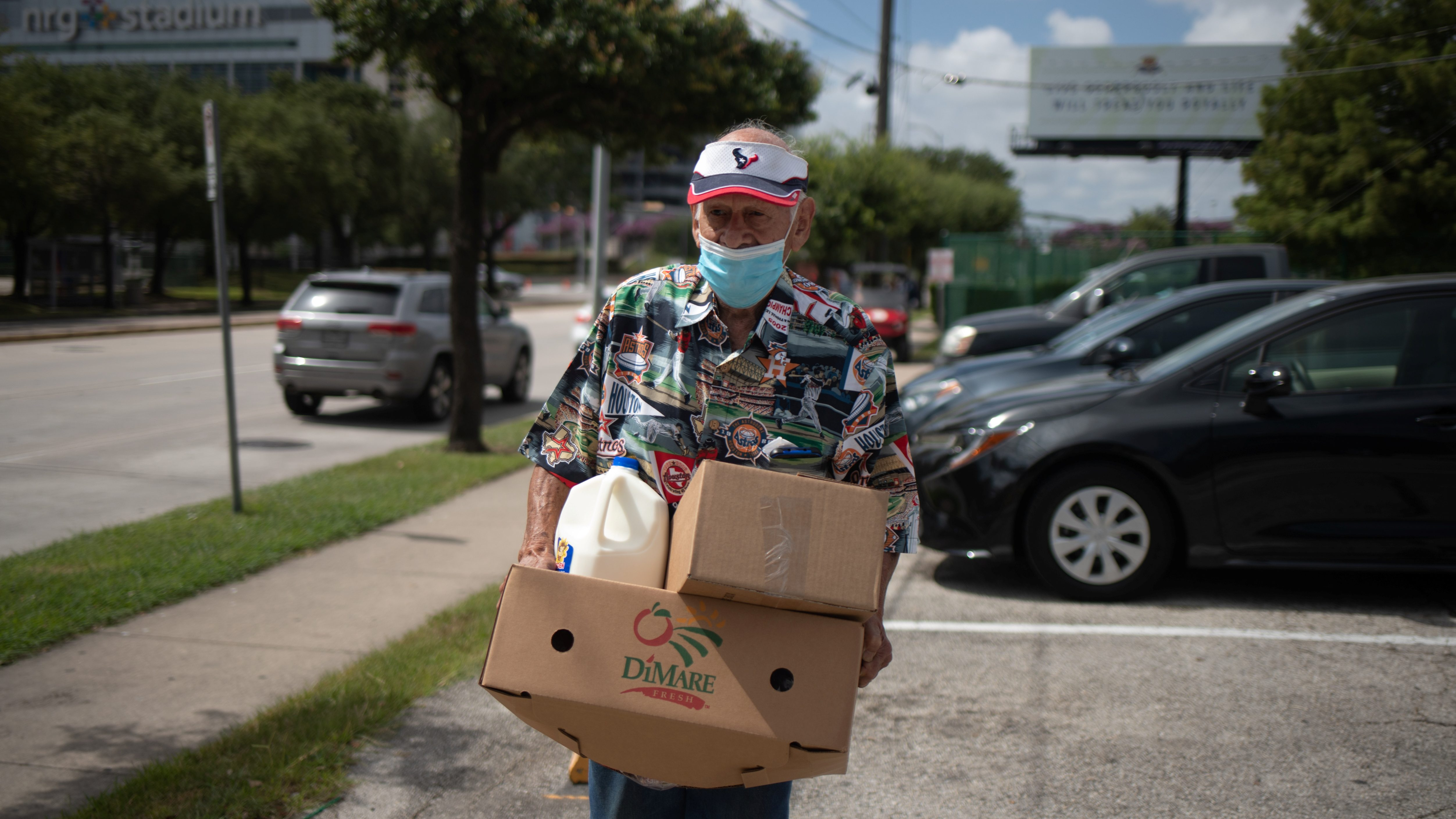 A man carries groceries from a food bank.