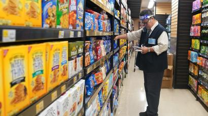 A worker with a face shield checks products on the shelf of a grocery store in the Manhattan borough of New York City, New York, U.S., August 7, 2020. REUTERS/Carlo Allegri