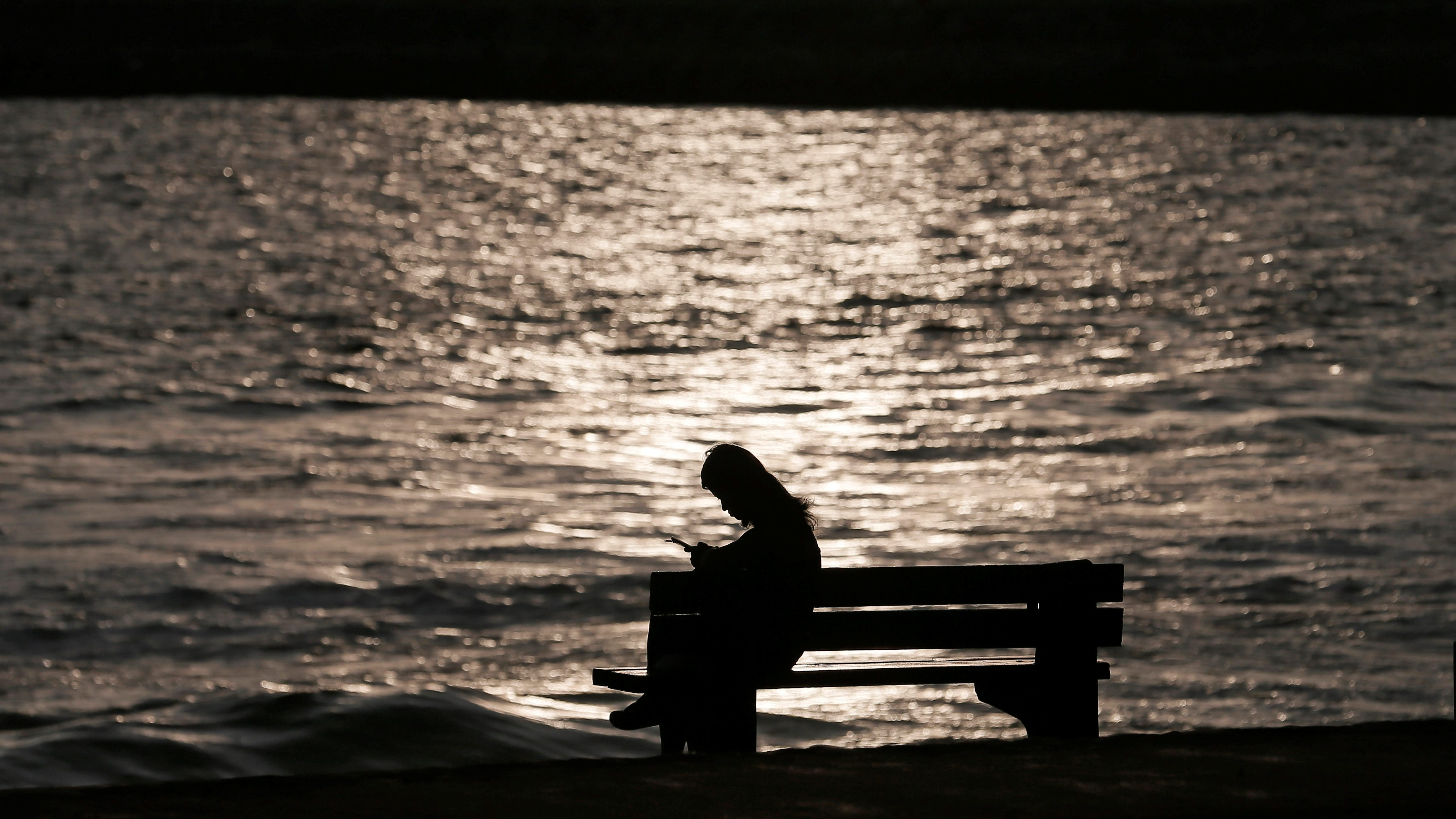A woman sits alone on a bench while using her mobile phone as the sun sets at a beach.