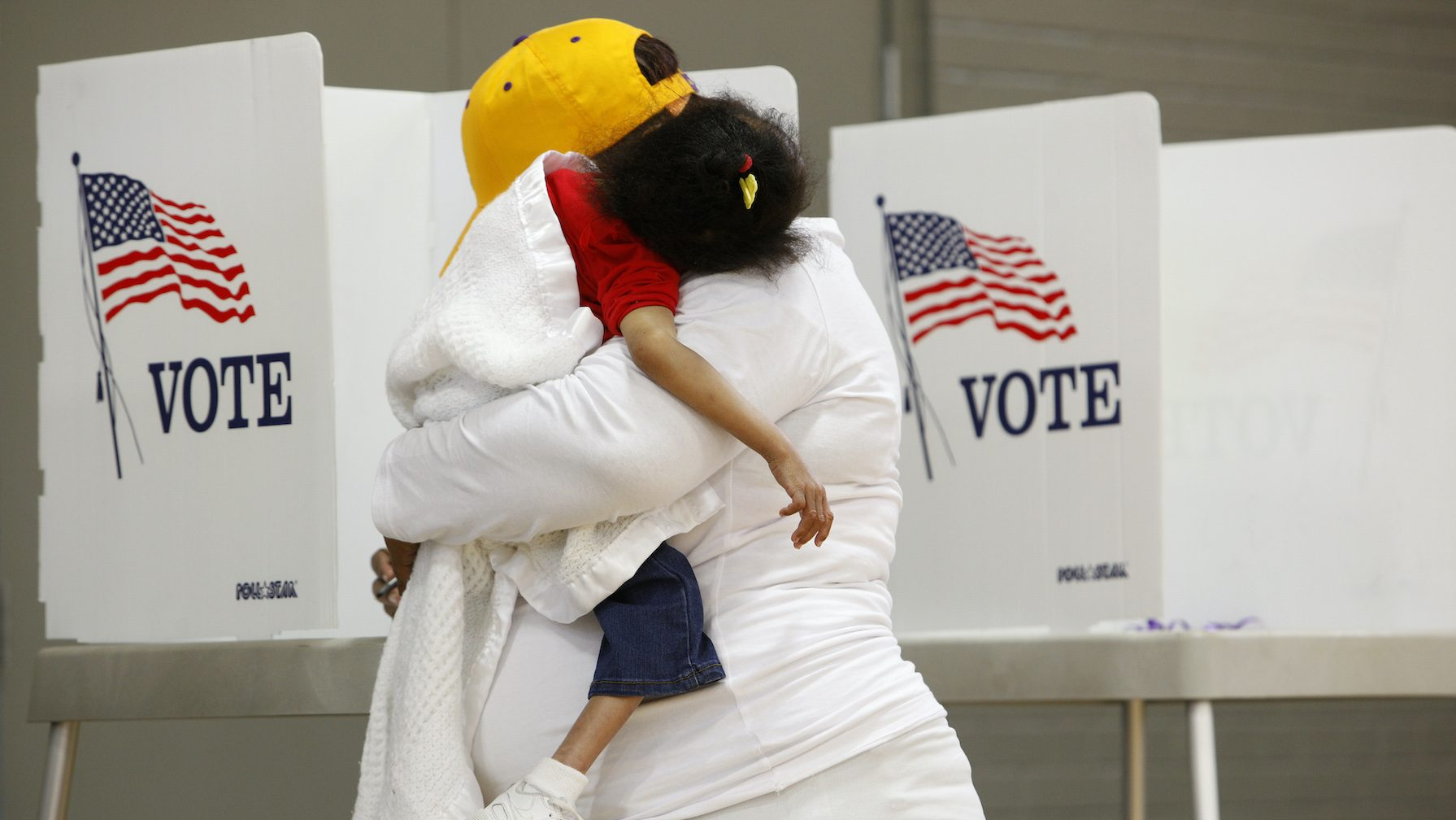 A mother carries her sleeping child while voting during the U.S. general election in Greenville, North Carolina
