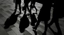 Workers cast shadows as they walk in Sydney
