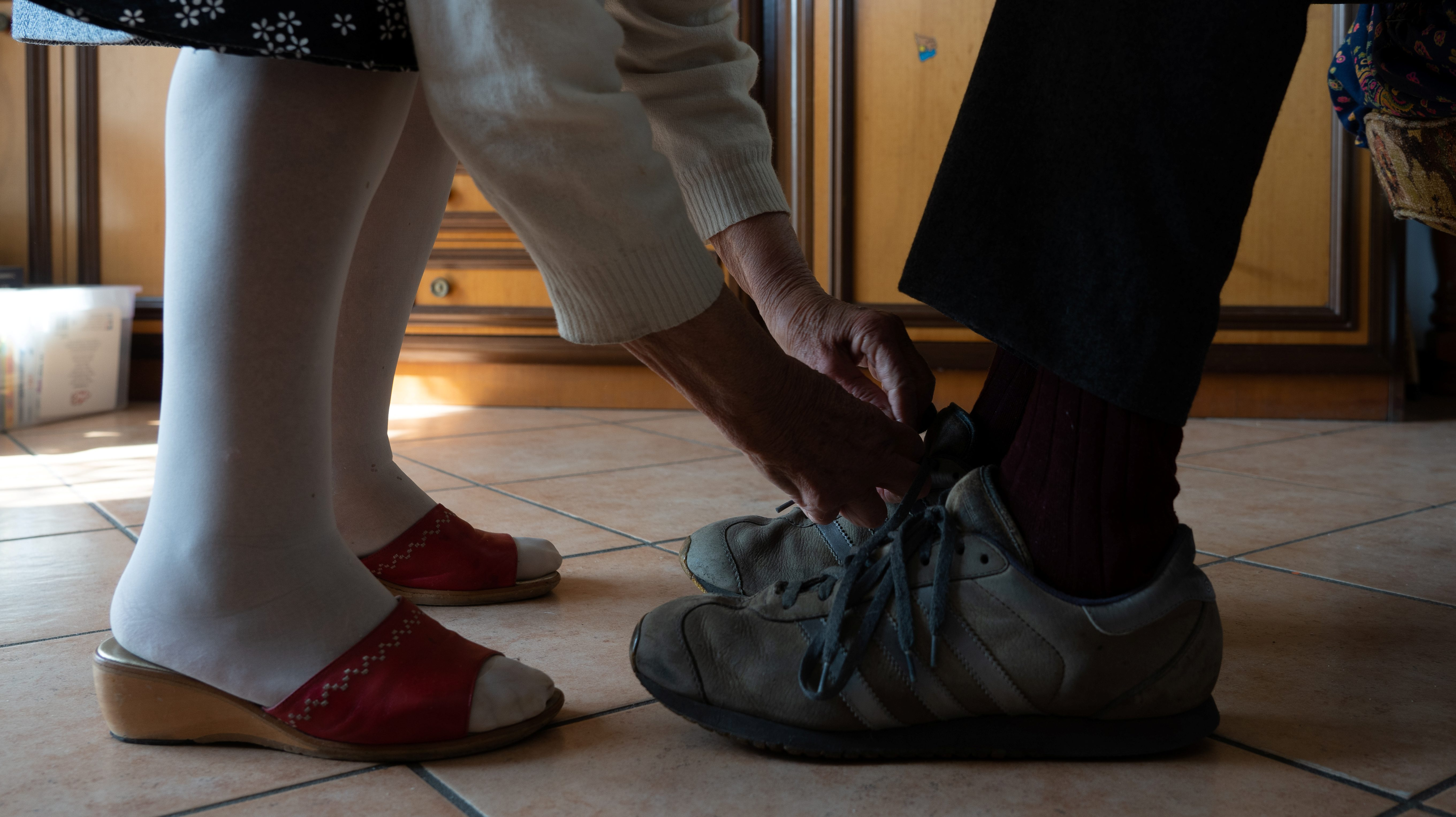 A person in stockings is tying the shoes of a person wearing sneakers.