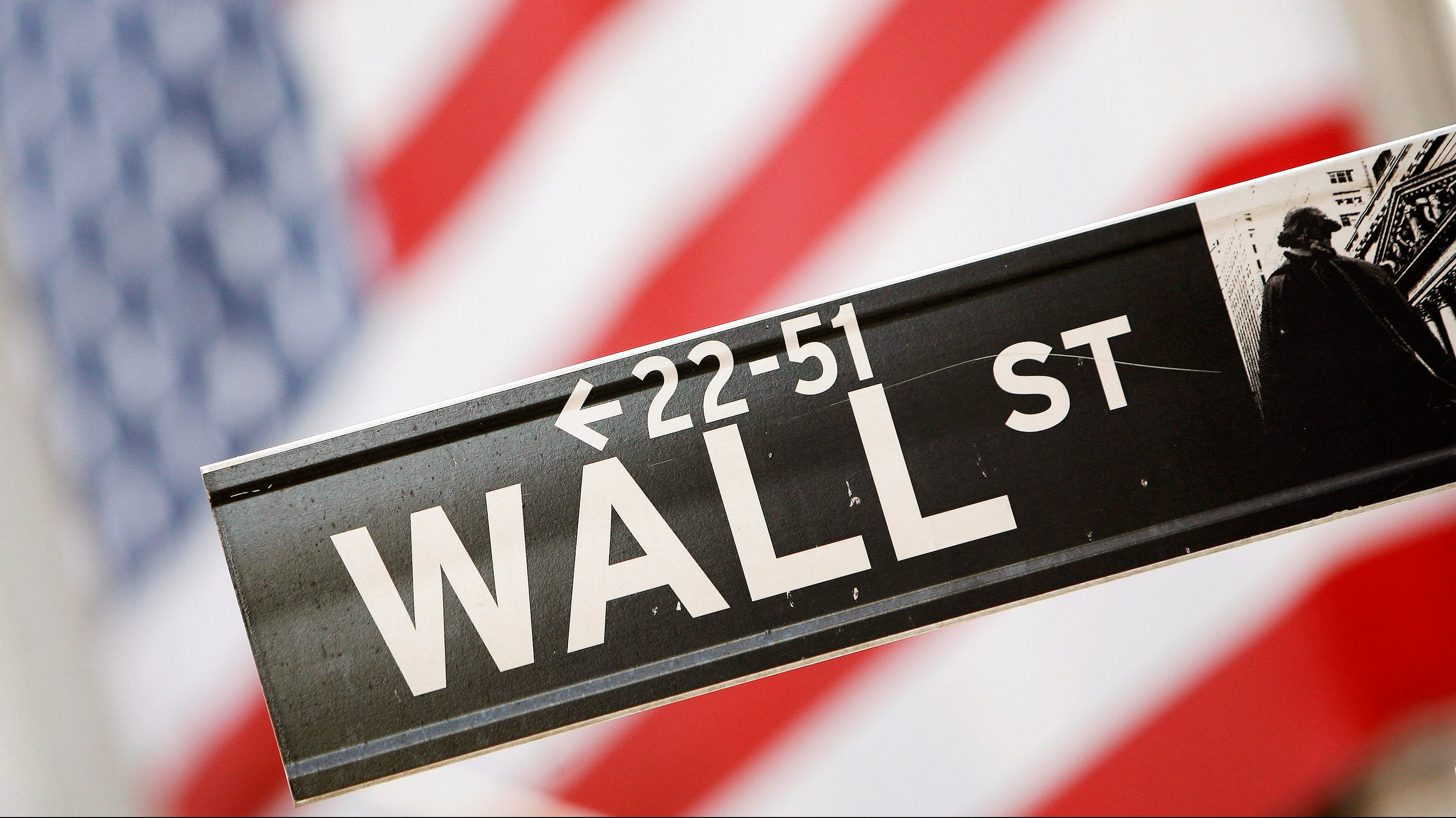 Wall Street street sign with American flag behind it.
