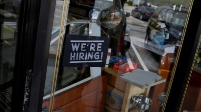 """A sign hangs in a shop window reading """"We're hiring!"""""""