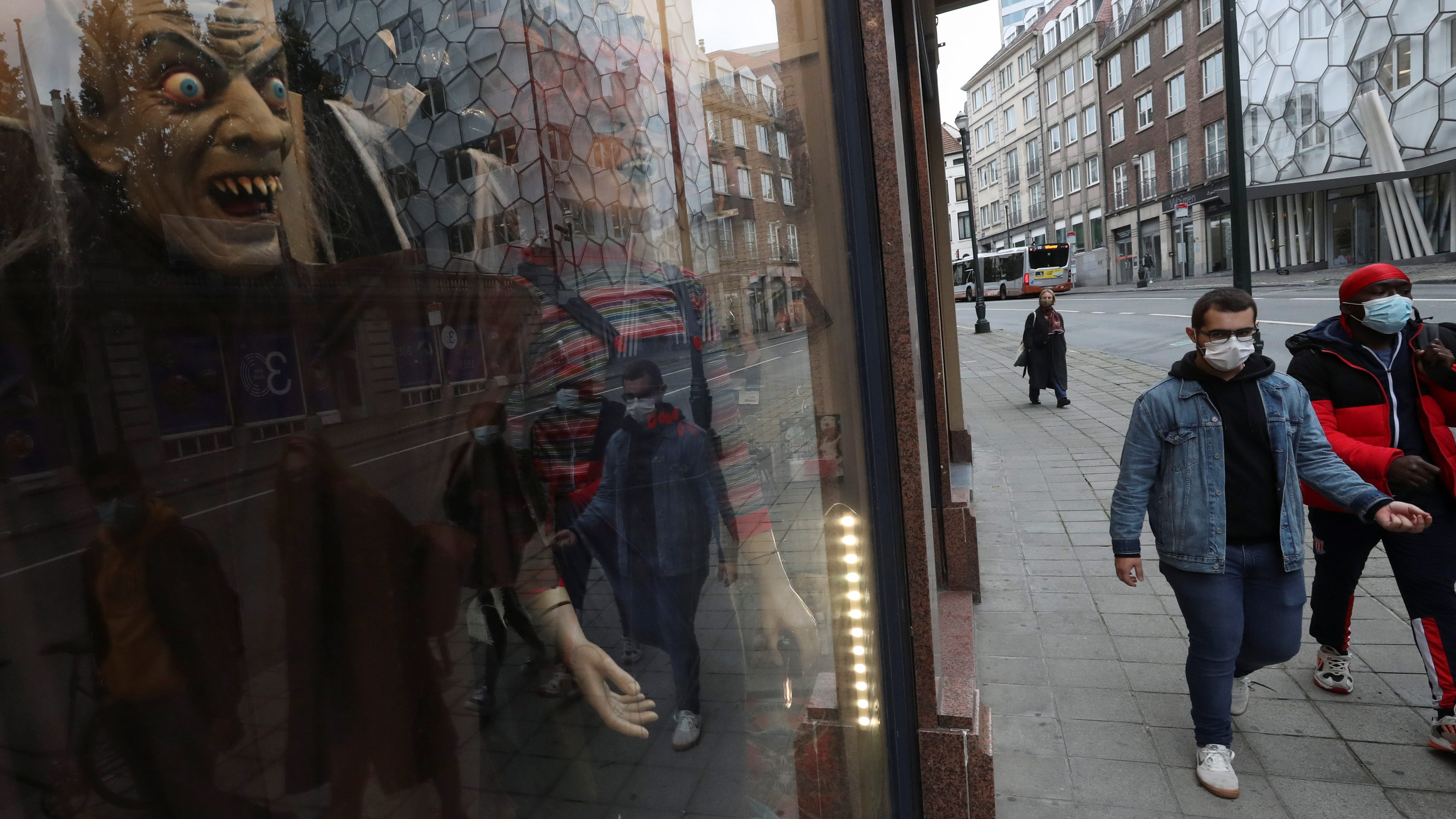 People wearing face masks walk past a store selling Halloween costumes near Brussels' Grand Place square, as the spread of the coronavirus disease (COVID-19) continues, in Belgium, October 13, 2020.