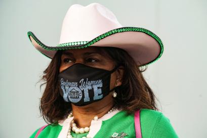 "A woman with a cowboy hat wears a mask reading ""vote"""