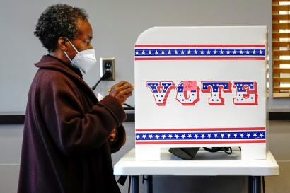A person stands in a voting booth in Milwaukee