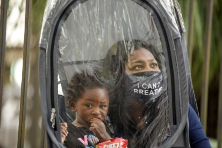 """Dana Clarke, wearing an """"I can't breathe"""" mask, holds her son inside a clear protective suit as she waits to vote early."""