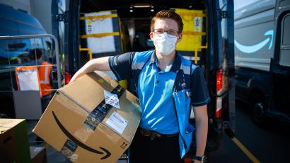 A delivery worker in a mask holds an Amazon Prime package